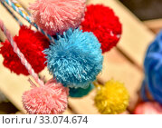 Fluffy pom poms with multi-colored threads. Стоковое фото, фотограф Nunik Varderesyan / Фотобанк Лори