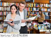 Купить «Girl reading book in bookstore while guy looking at her book ove», фото № 33074894, снято 18 января 2018 г. (c) Яков Филимонов / Фотобанк Лори