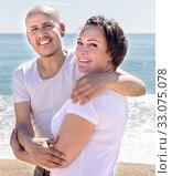 elderly man with a woman in white shirts cuddling on sand on beach. Стоковое фото, фотограф Татьяна Яцевич / Фотобанк Лори