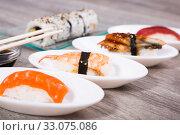 four kinds Nigirisushi on oval saucers and Uramaki. Стоковое фото, фотограф Татьяна Яцевич / Фотобанк Лори