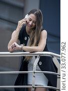 Купить «Beautiful stylish woman talking smartphone smilingly and looking at wristwatch checking time.», фото № 33077962, снято 6 августа 2020 г. (c) easy Fotostock / Фотобанк Лори