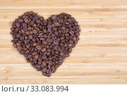 Кофейные обжаренные зерна, выложенные в форме сердца на деревянной доске. Стоковое фото, фотограф Игорь Долгов / Фотобанк Лори