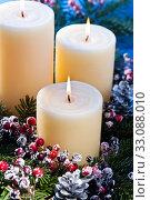 Купить «Three candles in an advent flower arrangement», фото № 33088010, снято 2 апреля 2020 г. (c) PantherMedia / Фотобанк Лори