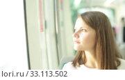 Купить «Young woman in casual clothing traveling in public transport», видеоролик № 33113502, снято 19 сентября 2019 г. (c) Яков Филимонов / Фотобанк Лори