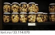 Купить «Glass jars with assorted preserved mushrooms on shelves in store», видеоролик № 33114070, снято 5 июля 2020 г. (c) Яков Филимонов / Фотобанк Лори