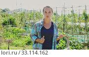 Купить «Portrait of smiling young woman standing in summer homestead», видеоролик № 33114162, снято 16 февраля 2020 г. (c) Яков Филимонов / Фотобанк Лори