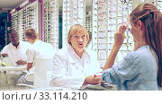 Купить «Mature female optician helping client to choose a spectacles in medical shop», видеоролик № 33114210, снято 4 июля 2020 г. (c) Яков Филимонов / Фотобанк Лори