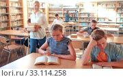 Купить «Teenage pupils sitting at table and studying, teacher in classroom», видеоролик № 33114258, снято 27 мая 2020 г. (c) Яков Филимонов / Фотобанк Лори