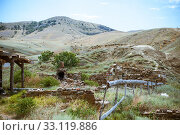 Купить «Old ruined log house and stone stove in the yard in Crimean steppe on a background of mountains», фото № 33119886, снято 20 июля 2016 г. (c) katalinks / Фотобанк Лори
