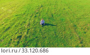 Купить «Low orbital flight around man on green grass with notebook pad at yellow rural field.», видеоролик № 33120686, снято 13 марта 2019 г. (c) Александр Маркин / Фотобанк Лори