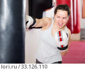 Купить «Enthusiastic sportswoman in the boxing hall practicing boxing punches with boxing bag», фото № 33126110, снято 5 мая 2017 г. (c) Яков Филимонов / Фотобанк Лори