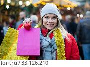 Купить «Cheerful female customer with Christmas gifts on street», фото № 33126210, снято 1 декабря 2018 г. (c) Яков Филимонов / Фотобанк Лори