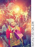 Купить «Happy girl chooses Christmas toys on the street market», фото № 33126234, снято 1 декабря 2018 г. (c) Яков Филимонов / Фотобанк Лори