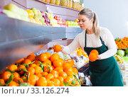 Купить «Adult female in apron selling fresh oranges», фото № 33126274, снято 1 апреля 2020 г. (c) Яков Филимонов / Фотобанк Лори
