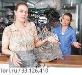 Купить «Dissatisfied client of dry cleaning», фото № 33126410, снято 9 мая 2018 г. (c) Яков Филимонов / Фотобанк Лори