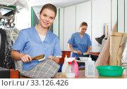 Купить «Girl working in dry cleaning», фото № 33126426, снято 9 мая 2018 г. (c) Яков Филимонов / Фотобанк Лори