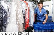 Купить «Girl working in dry cleaning», фото № 33126434, снято 9 мая 2018 г. (c) Яков Филимонов / Фотобанк Лори