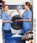 Купить «Two girls working in dry cleaning», фото № 33126442, снято 9 мая 2018 г. (c) Яков Филимонов / Фотобанк Лори