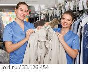 Young workers of laundry holding clean garment. Стоковое фото, фотограф Яков Филимонов / Фотобанк Лори