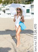 Купить «Young female in swimsuit with umbrella and bag walking at beach», фото № 33126470, снято 10 июля 2018 г. (c) Яков Филимонов / Фотобанк Лори