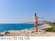 Стройная девушка в лёгком платье стоит на берегу моря. Редакционное фото, фотограф Юрий Морозов / Фотобанк Лори