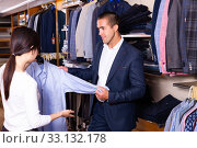 Купить «Seller helps buyer to choose a shirt in the store», фото № 33132178, снято 25 февраля 2020 г. (c) Яков Филимонов / Фотобанк Лори