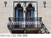 A fragment of the building's facade with Venetian Windows and a balcony with a metal decorative grille. Burano, Venice, Italy (2017 год). Редакционное фото, фотограф Наталья Волкова / Фотобанк Лори