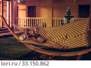 Slender beautiful young woman in a swimsuit is lying on a wicker hammock in the yard of the garden in summer. Стоковое фото, фотограф katalinks / Фотобанк Лори