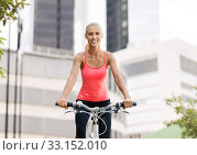 happy young woman riding bicycle at city. Стоковое фото, фотограф Syda Productions / Фотобанк Лори