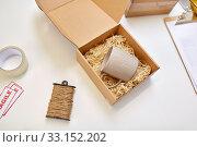 Купить «parcel with straw filler and mug at post office», фото № 33152202, снято 11 января 2019 г. (c) Syda Productions / Фотобанк Лори