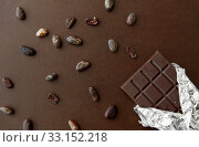 Купить «dark chocolate bar in foil wrapper and cocoa beans», фото № 33152218, снято 1 февраля 2019 г. (c) Syda Productions / Фотобанк Лори