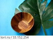 Купить «close up of wooden plate and monstera leaf», фото № 33152254, снято 16 ноября 2018 г. (c) Syda Productions / Фотобанк Лори
