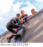 Купить «Russia, Samara, June 2019: a young sports man with the help of a rope overcomes the most difficult obstacles in the race of Everest heroes.», фото № 33157234, снято 8 июня 2019 г. (c) Акиньшин Владимир / Фотобанк Лори