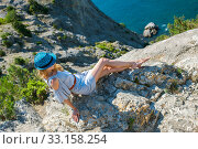 A young woman in a summer dress sits on the edge of a mountain or cliff with a beautiful sea view. Стоковое фото, фотограф katalinks / Фотобанк Лори