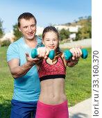 Купить «Girl with father exercising with dumbbells», фото № 33160370, снято 29 сентября 2018 г. (c) Яков Филимонов / Фотобанк Лори
