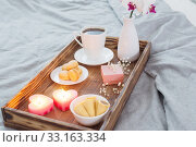 Купить «Coffee, sweets, candles, flowers and girt on wooden tray on bed. Concept with Valentines day», фото № 33163334, снято 14 января 2020 г. (c) Майя Крученкова / Фотобанк Лори
