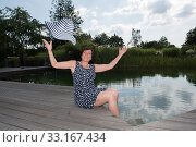attractive woman siiting with legs in  the pool and throwing her hat. Стоковое фото, фотограф Jürgen Hüls / PantherMedia / Фотобанк Лори