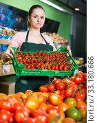 Купить «Saleswoman with crate with tomatoes in supermarket», фото № 33180666, снято 14 октября 2017 г. (c) Яков Филимонов / Фотобанк Лори