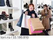Portrait of adult woman which is showing purchases in shoes store. Стоковое фото, фотограф Яков Филимонов / Фотобанк Лори