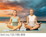 Купить «women doing yoga and meditating in lotus pose», фото № 33196494, снято 28 июля 2019 г. (c) Syda Productions / Фотобанк Лори