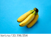 close up of ripe banana bunch on blue background. Стоковое фото, фотограф Syda Productions / Фотобанк Лори