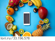 Купить «exotic fruits around smartphone on blue background», фото № 33196578, снято 16 ноября 2018 г. (c) Syda Productions / Фотобанк Лори