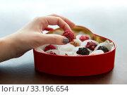 Купить «hand with candies in heart shaped chocolate box», фото № 33196654, снято 1 февраля 2019 г. (c) Syda Productions / Фотобанк Лори