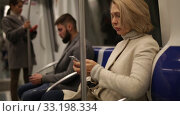Portrait of mature woman absorbed in her smartphone while traveling in subway car. Стоковое видео, видеограф Яков Филимонов / Фотобанк Лори