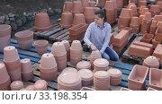 Купить «Female customer is standing near clay pots in stock», видеоролик № 33198354, снято 8 ноября 2019 г. (c) Яков Филимонов / Фотобанк Лори