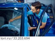 Купить «Worker in uniform puts the seat cover, car service», фото № 33203694, снято 27 ноября 2019 г. (c) Tryapitsyn Sergiy / Фотобанк Лори