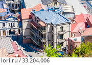 Купить «View of the roofs of houses in the center of Tbilisi. Old city and tiled roofs in Georgia», фото № 33204006, снято 5 августа 2020 г. (c) Николай Коржов / Фотобанк Лори