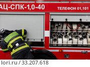 Сотрудник МЧС закрывает боковую дверцу пожарной машины в городе Москве, Россия (2020 год). Редакционное фото, фотограф Николай Винокуров / Фотобанк Лори