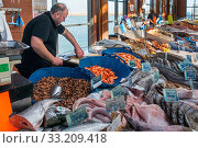 Counter with fresh fish and shrimps on display at covered fish market in the port at seaside resort Port-en-Bessin, Calvados, Normandy, France, 2019. Стоковое фото, фотограф Philippe Clement / Nature Picture Library / Фотобанк Лори