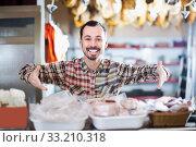 Smiling man butcher showing sorts of meat. Стоковое фото, фотограф Яков Филимонов / Фотобанк Лори